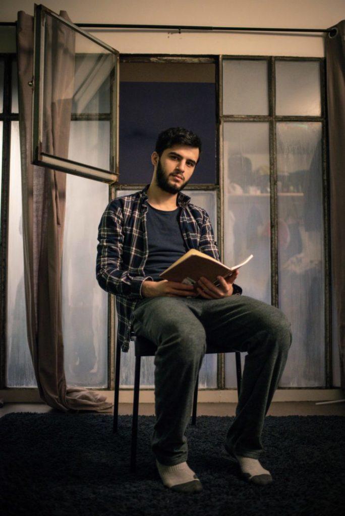 Portrait photo de Zaher Azzaher (Syrie), 22 ans, dans sa chambre à la Maison des journalistes, à Paris